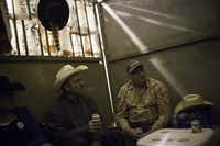 Barrel setter Lorna Paden (left), driver Fred Ewing and driver Rene Salmond relaxed in their stall after the chuck wagon races on Thursday.