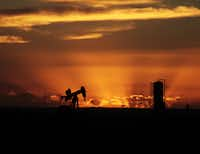 Oil well pumpjacks are scattered about the sparse landscape in Loving County, Texas.