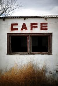 A building that used to be a cafe in Mentone, Texas, is now overgrown with brush.