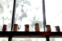 Vintage creamers  line a window ledge in the breakfast nook.