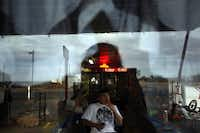 Clerk Charles Vela watches television while waiting for customers at the Hopper Gas Station in Mentone.