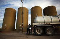 Agustin Munoz fills his semi with salt water to be used at one of the oil fields in Loving County, Texas. Munoz is one of the approximately 300 workers who work in Loving County and stay in the neighboring cities of Odessa or Pecos.