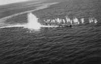 """From """"Blackett's War,"""" by Stephen Budiansky: """"U-118 under depth charge and machine gun attack by aircraft from the U.S. escort carrier Bogue, June 12, 1943."""""""