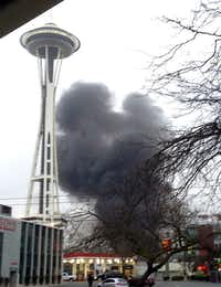 In this photo provided by KIRO- TV,  black smoke billows skyward from the scene of a helicopter crash Tusday outside the KOMO-TV studios near Seattle's Space Needle. KOMO-TV said the chopper was coming in for a landing on the roof of its studio when it possibly clipped the building before going down.KIRO-TV - via AP