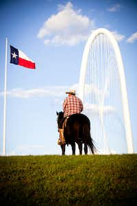 Reynaldo Guerra watches the Margaret Hunt Hill Bridge festivities from atop his horse while riding the Trinity River levees on March 3 in West Dallas.
