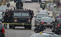 Police officers in tactical gear arrive on an armored vehicle as they surround an apartment building during the search for the second Boston marathon bombing suspect Friday morning in Watertown, Mass. One of the suspects died after a shootout with police, and much of the Boston area was shut down as police searched for the second.Charles Krupa - The Associated Press