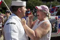 Petty Officer 2nd Class Johnny Parenteau, 23, greets his mother, K.C. Parenteau, after hopping off a float during Friday's Fourth of July parade in Arlington. Parenteau had told his parents his leave had been canceled in order to spring the surprise.David Woo - Staff Photographer