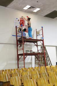 Tumi Mphahlele (left), 19, and Marissa Miller, 22 repaint the school's crest in the auditorium. Niether of the girls are members of the Village Church, but came to help revitalize the northwest Dallas school.