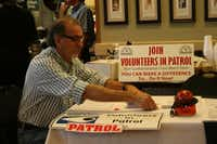 Santiago Hinojosa readies a volunteer information table at the Northeast Division of the Dallas Police Department's Wellness & Safety Breakfast on June 25. Hinojosa said he participates in the division's Volunteers in Patrol program about two or three times a month with his wife, Cecilia.HEATHER NOEL - neighborsgo staff