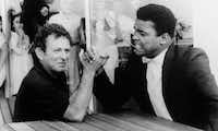 Novelist Norman Mailer is shown arm wrestling with heavyweight champion Muhammad Ali on the terrace of their San Juan hotel, in this August 1, 1965 file photo.