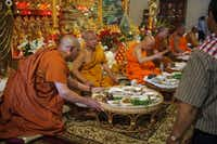 Buddhist monks receive food from the congregation during Lao New Year at Wat Lao Siribuddhavas Temple in Royse City on April 20. The celebration was filled with food, worship and festivals.Matthew Busch - Staff Photographer