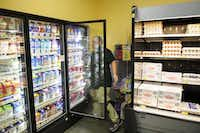 Orlando Guajardo rearranges items in the display refrigerators at the Wal-Mart store off Greenville. Trader Joe's, Sprouts Farmers Market and WinCo Foods have put pressure on Wal-Mart, Kroger, Tom Thumb and Target.Matthew Busch  -  Staff Photographer