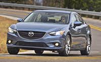 Unlike most front-wheel-drive cars, the 2014 Mazda6 Grand Touring has a long, broad hood and curved top that give it the aggressive proportions of an upscale rear-wheel-drive sedan.