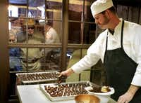 Kevin Wenzel, chocolatier and co-owner of Wiseman House Chocolates, makes truffles in the back of Bliss Living boutique as customers watch in Hico, Texas,Courtney Perry