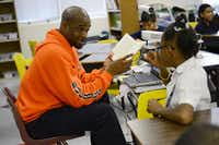 North Dallas High School athletic director Carlton Dixon reads a book to fourth-grade students at Onesimo Hernandez Elementary School. Dixon started the new Neighborhood Bulldogs program.Staff photo by ROSE BACA