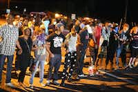 FERGUSON, MO - AUGUST 13:  Demonstrators protest the shooting death of teenager Michael Brown on August 13, 2014 in Ferguson, Missouri. Brown was shot and killed by a Ferguson police officer on Saturday. Ferguson, a St. Louis suburb, is experiencing its fourth day of violent protests since the killing.  (Photo by Scott Olson/Getty Images)Scott Olson - Getty Images