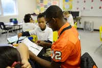 Junior Desmond Davisa football player at North Dallas High School, tutors fourth-grader Rayvion Scott at Onesimo Hernandez Elementary School. He is part of the new Neighborhood Bulldogs program.Staff photo by ROSE BACA