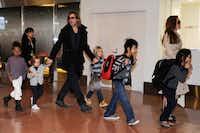 Stars on the move: Brad Pitt and Angelina Jolie escort their kids through Haneda Airport in Tokyo last November.