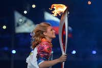 Russian tennis star and Olympic medalist Maria Sharapova runs with the torch at the Fisht Olympic Stadium.ALBERTO PIZZOLI - AFP/Getty Images