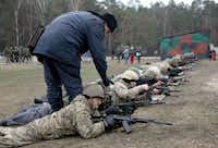 """A Ukrainian interim forces officer supervises recruits during a shooting exercise not far from Kiev. Ukraine's parliament on Monday approved the partial mobilization of troops to counter """"Russian interference"""" on its soil.Anatolii Stepanov  - Presse"""