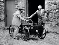 FILE - In this Dec. 10, 1936 file photo, Henry Ford, right, stands with his first car built in 1892, assembled in the brick barn in the background in Detroit. At left is James Bishop. The Detroit auto show, which opens to the public Jan. 18 after a week of media and industry previews, dates to 1907, when a group of dealers held a show in a city park.  (AP Photo/FILE)Uncredited - AP