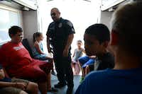 Sgt. Oscar Cantu, of the Rowlett S.W.A.T. team, talks to children inside the tactical truck during the first youth police academy. The first of two week-long ÒacademiesÓ was geared toward fifth- through- eight grade students interested in exploring law enforcement careers.