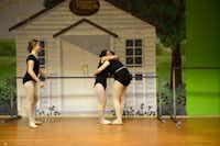 Carlee Baladez gets a hug from Carly Buchanan, 16, while Darby Watson, 12, looks on, during practice.ROSE BACA/neighborsgo staff photographer
