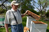 Lewis tends to one of his bee hives.Rose Baca - neighborsgo staff photographer