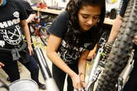 Eighth-grader Lezly Padilla fixes the gears on a bicycle during Garland ISD's after-school program.ROSE BACA/neighborsgo staff photographer