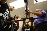 Sixth-grade Social Studies teacher Steven Smith helps students (from left) Patrick McGregor, Anthony Cruz and Diego Gomez repair a bicycle during Garland ISD's after-school program.ROSE BACA/neighborsgo staff photographer