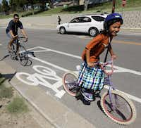 Valentin Rodriguez rides with his daughter Sophia, 7, in the city's first nonshared bike lane on Mary Cliff Road in Oak Cliff.