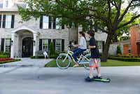 Grant Waco, 7, and his sister Avery, 13, play in the driveway of their University Park home, while their mother watches. The family d moved from North Dallas to University Park, which ranked second in the poll.