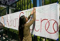 An El Monte High School student hangs a banner for senior Adrian Castro, who was killed when the Humboldt State University-bound bus he was on crashed in Orland.Damian Dovarganes - AP