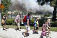 Residents on Docena Road in Carlsbad, Calif., walk with burning brush behind them Wednesday, May 14, 2014. Thousands were asked to evacuate their homes in Carlsbad after the blaze erupted at about 10:34 a.m. Wednesday and spread through rapidly heavy brush before jumping into residential areas. (AP Photo/U-T San Diego, John Gibbins)John Gibbins - AP