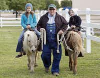 Hannah Greer (left), 10, of Allen, and Wade Bishop (right), 3, of Plano, are led by Tony Scalise, 69, of McKinney, who operates Texasponyrides.com at the the Collin County Farmers Market in Plano, which was having their opening day on Saturday, April 20, 2013.Stewart F. House - Special Contributor