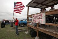 Robert Stephens of Rowlett volunteered to hold the U.S. flag during the national anthem prior to the mud-bogging races at The Pits in Nevada, Texas.Stewart F. House - Special Contributor