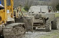 """Michael Gray of Royse City peeks out of his truck, """"Harms Way,"""" as he gets a tow after breaking down in the mud at the Nevada Mud Pits.Stewart F. House - Special Contributor"""