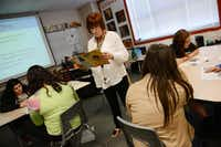 "Karen Martin, a seventh-grade language arts teacher, reads an article to students during ""Cain Time.""Rose Baca - neighborsgo staff photographer"