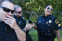 Officers Dan Lacy (left) and David Grubbs Jr. joked with Sgt. Tracy Jones after they set a timer to record an upcoming episode. The department liked the series overall.