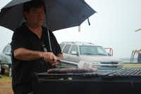J.D. Ryan cooks bratwursts and hot dogs in the rain Sunday at Meadowmere Park on Grapevine Lake. Ryan lent a hand to the Super Hero Foundation of Texas's first event.