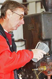 John Burgoyne of Azle, Texas loads up the Turn of the Century Foos gas engine with some fuel before giving the flywheel a good whirl to start it up. Burgoyne adores working with the antique engines and restoring them to good working order.