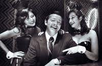 Dallas Playboy Club owner Carroll Davis (center) at the club with playmates Debbie Gonzales (left) and Elaine Oxman (right) on September 28, 1981.