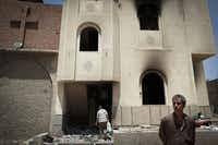 Coptic Christians walk outside of a burned church building near the destroyed New Church of the Virgin Mary, about 70 miles south of Cairo in the village of El Nazla, Egypt.