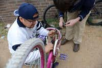 """Armando Ramirez fixes a donated, used bike for his daughter during a """"Wrench Day"""" as part of the Earn-A-Bike program in Irving.Rose Baca - neighborsgo staff photographer"""