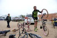Earn-a-Bike volunteer Jacob Salassi gets ready to help James Alfaro, 9, fix a used bike.Rose Baca - neighborsgo staff photographer