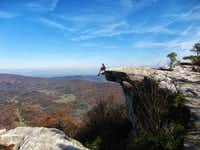 An Appalachian Trail hiker rests on a rocky outcropping on McAfee's Knob, from which you can enjoy views of the Catawba Valley and Blue Ridge Mountains.