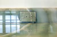 Painter Joe Mear copied the color and veining of jade-green-onyx bath counters on a switch plate.