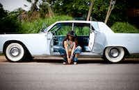 Erykah Badu nestled between the suicide doors of her 1964 Lincoln Continental