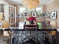 """""""This is a dining room that people will actually hang out in for a cocktail party, so it gives the space more use,"""" says Flannery, who achieved a gallery effect by wrapping the room with a window-ledge-height picture shelf. The gold-and-crystal Bollywood chandelier presides over a Knoll desk repurposed as dining table. The Starck Lucite chairs are paired with two Louis-style antique chairs from Debris. The room was painted eight times before Flannery found a satisfying shade of taupe."""