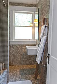 The bathroom was redone by Dallas designer Murray Woodall with custom glass tiles, a fog-proof heated medicine cabinet and rustic ladder from Sticks and Stones Outdoor Living.